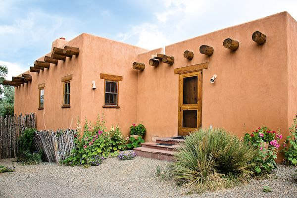 Characteristics of Pueblo homes: example pueblo house with flowers.